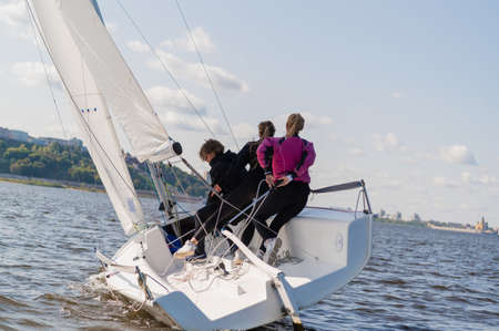 A fast, sporty, single-masted yacht with three athletes on board sails with a fair wind on a beautiful river