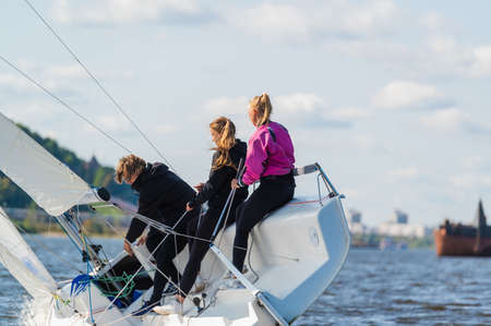 A young sailing instructor conducts a class with two female novices on a river with a beautiful landscape Zdjęcie Seryjne