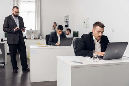 The senior Manager checks the quality of tasks performed by his Junior employees sitting at a computer in the office of a financial company.