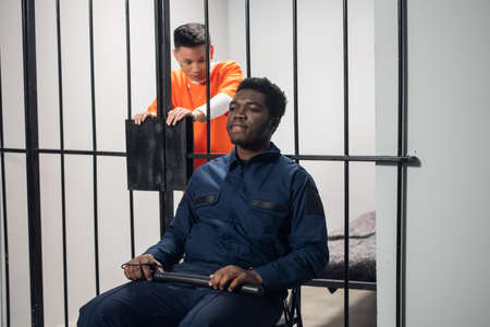 Strong black man an overseer in the prison guards the Chinese mafia threat in the red robe