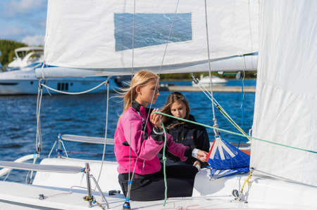 Cute blondes on the pier prepare a sailing yacht for a regatta, pull the sail on the mast with ropes.
