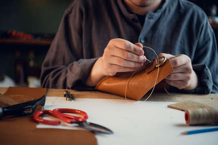 Sitting at a table in the workshop a young guy manually sews leather elements to each other. Stock Photo