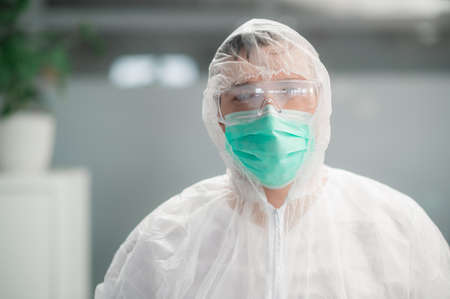 Portrait of an unrecognizable doctor, in a medical protective suit and mask.