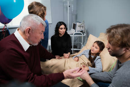 A family sitting around a little girl in her hospital ward and talking. Banque d'images