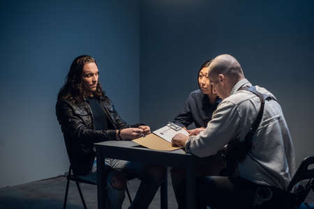 A tough police detective interrogates a crime suspect with a tattooed face in an interrogation room
