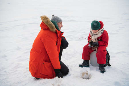 An experienced fisherman father teaches his young son to handle gear for winter fishing, they made a hole and fish in it
