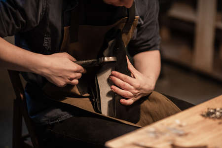 a hereditary shoemaker makes shoes from leather in the family workshop