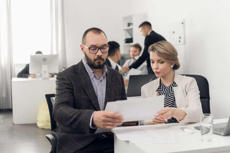 The Director of the company in a jacket gives instructions and tasks to young colleagues in the office of a trading company