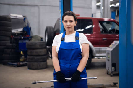 Car service worker mechanic holding tools and posing