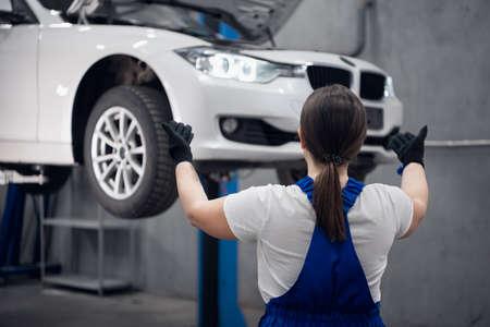 Woman raises a car above the ground using telepathy Banco de Imagens