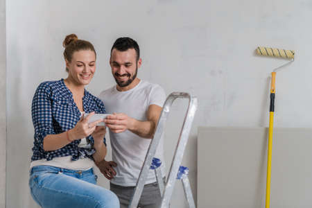 Man and woman sitting on a stepladder and looking at photos on the phone
