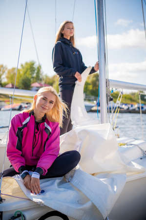Two girls decided to spend a weekend on the river, preparing the yacht to go out on the water