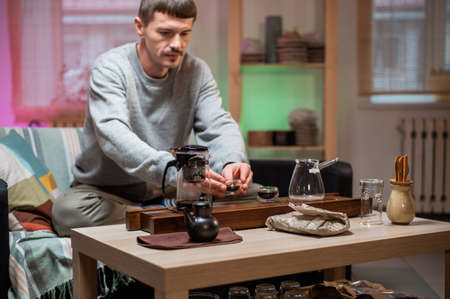 A man brews chinese tea according to an old oriental recipe on a bamboo gongfu tray. Adds boiling water from the teapot to the teacup.