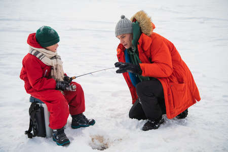 Father and son in red winter clothes came to fish on the river bank in winter