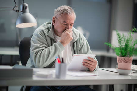 During the coronavirus pandemic, an adult male in an office sits at a desk, reads documents, and has a runny nose Stock Photo