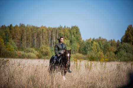 Cute girl equestrian instructor rides a horse in an equestrian club Standard-Bild