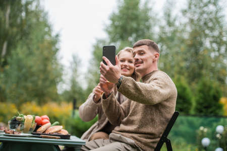 Video conference with friends in the open air during a picnic in nature with beer and barbecue. Young people use their smartphone to chat with friends and have fun.