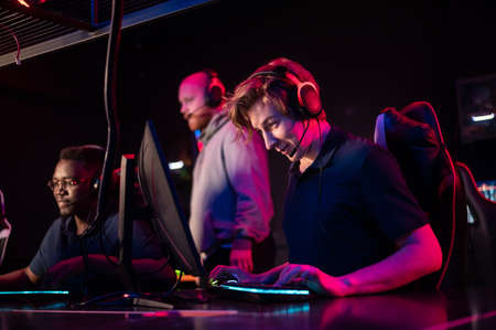 Friends come to the computer club and play online games under the guidance of an experienced cyber instructor Stock Photo