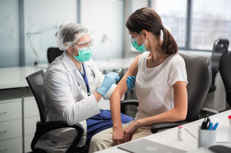 A young woman in a mask decided to get vaccinated against the coronavirus during the pandemic by an experienced doctor in the laboratory Banque d'images