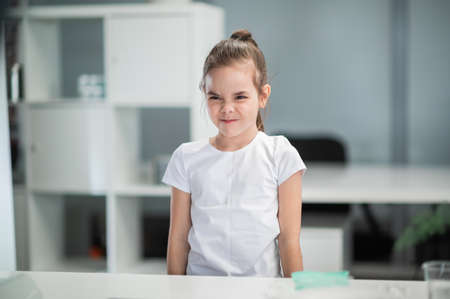 Portrait of a little girl in a white T-shirt on the background of a shelf, the girl wrinkles her nose, she is dissatisfied Banque d'images