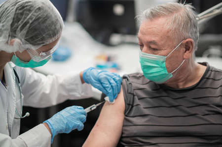An experienced female doctor gives an injection in the shoulder with the covid-19 coronavirus vaccine to an elderly male patient
