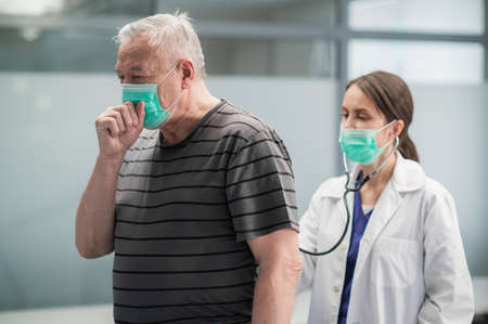 The gray-haired patient of the clinic suffered from pneumonia, he coughs, the doctor listens to the wheezing in the lungs with a stethoscope