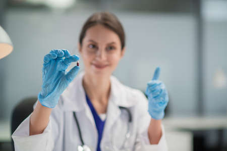 The doctor prescribes the medicine and presents the patient with its antiviral properties. A hand in a medical glove in the foreground