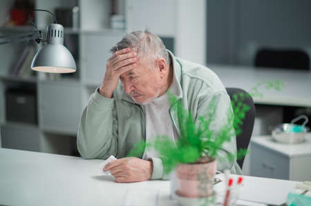 At the end of the working day, an elderly office worker felt a headache, he sits at his desk and holds his head