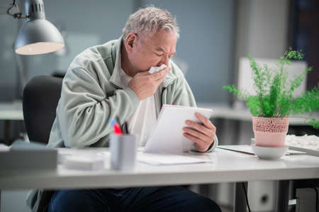 An elderly manager gets sick while working, he blows his nose and feels bad, sits at his desk and reads notes in a notebook Banque d'images