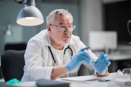 The famous experienced practicing medical professor holds an online conference for doctors from other cities and countries from his office at the university