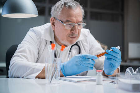 An experienced veterinarian doctor received a test sample of blood with an anti-virus injected into it. Preparing to examine it under a microscope Banque d'images