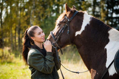 Tender communication between a rider and her horse before a riding lesson Banque d'images