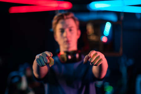 The hands of a young gamer pointing his fingers at the camera, the guy himself in blur