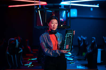 An experienced asian gamer shows a gaming keyboard and talks about its advantages