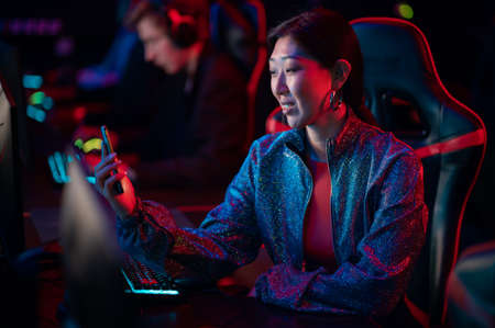 A pretty streamer girl is broadcasting on twitch from a dota tournament among esports players