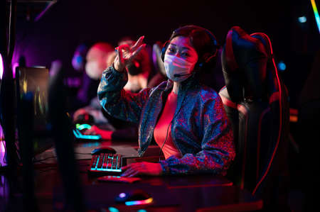 The tournament in the conditions of covid-19 is held in medical masks, gamers play at computers, the team leader is a chinese girl, shows a victory gesture