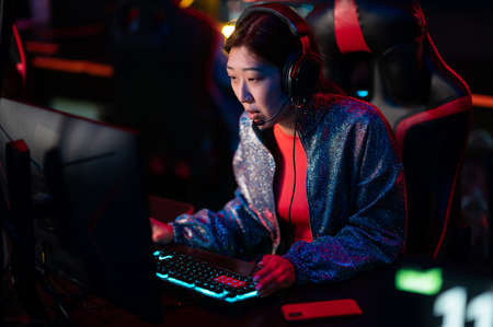 Training of esports players in a bootcamp. A young asian gamer at a powerful gaming PC looks at the monitor. Online cyber sports.