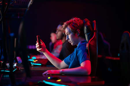 A young esports player records a video on his phone for his vlog from the training base of his team of gamers