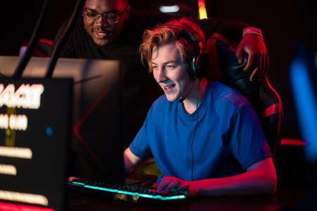 An experienced esports player shows his dark-skinned friend how to play an online video game in a computer club