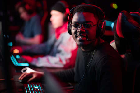 A member of the esports team at a bootcamp training session. Portrait of a black guy with glasses at a gaming computer with a glowing keyboard.