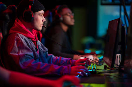 A multi-racial team of esports athletes conducts a training session before an online shooter tournament. Neon light. Banque d'images