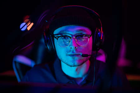 Close-up portrait of a young gamer at the computer. A gaming headset with headphones on the head. Neon light. The concept of esports.