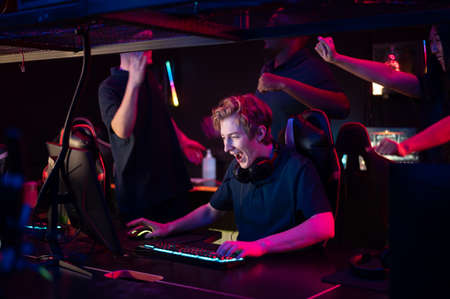 Two guys and a girl in medical masks in a computer club give support to their friend during his game