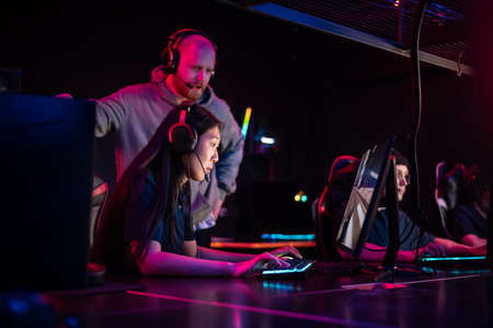 Esports team training camp in computer club with coach, caucasian guy and asian girl