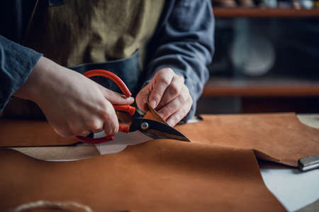 At the masterclass for the production of shoes, an experienced shoemaker cuts out leather with scissors