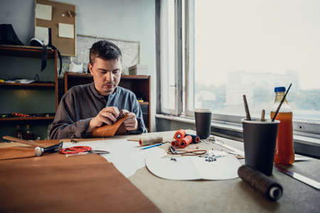Portrait of a professional shoemaker in the interior of a shoemakers workshop making a bag made of genuine leather Banque d'images