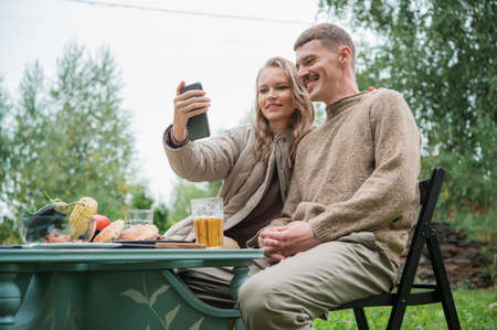 A young couple makes a very funny and emotional selfie, fooling around and making faces in front of the smartphone camera. They made an outdoor dinner with a grill and beer.
