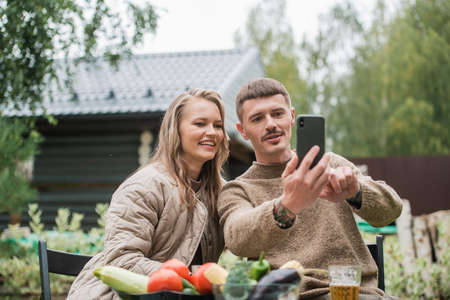 Selfies on a smartphone for social networks are made by a girl and a guy sitting at a picnic table in the fresh air in the countryside.