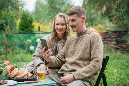 A young couple in their garden near the house communicates via video call on a smartphone with their parents, congratulates them on their wedding anniversary. Holiday table, picnic.