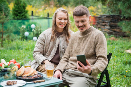 A young couple had a family dinner away from the city. Picnic with grilled meat and beer. They take photos of beautiful nature for their social media blog on their smartphone. Banque d'images